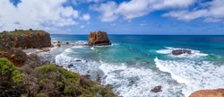 Australia. Great Ocean Road. A picturesque panorama of the ocean coast and rock bay. Stormy waves with white lambs roll ashore with sheer rocks. A clear sunny day. Blue sky with light clouds.