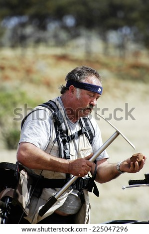 AUSTRALIA - MAY 6: Gold miner in the Australian outback looking to see if a piece of quartz containing gold,  may 6, 2007.