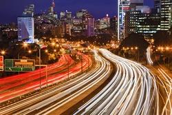 Australia NSW Sydney city Cahill expressway at sunset with long blurred traffic lights multi-lane motor road towards CBD, harbour bridge and illuminated landmarks