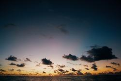 Australia sundown beach with clouds in the sky. Pink and blue sunlight illuminates the sky. Summer morning sundown over the sea background.