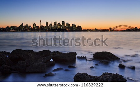 australia sydney CBD cityscape view over harbour at sunset with orange sky skyscrapers, bridge and blurred water