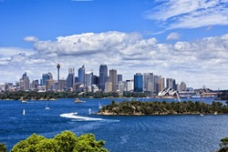 Australia Sydney city CBD view from Taronga zoo over harbour waters sunny bright summer day lush colours and white clouds in blue sky