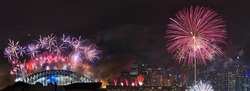 Australia SYdney New Year fireworks distant panoramic view of light show over city CBD and harbour bridge at midnight
