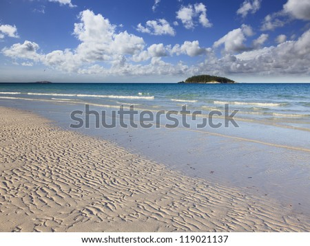 australia whitsunday island national park white sand beach with waves and islands on horizon under blue sky