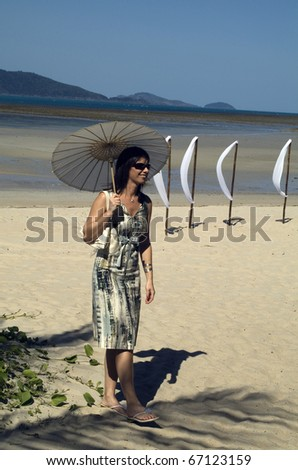 Australia, woman with sun umbrella on a beach on Hamilton Island