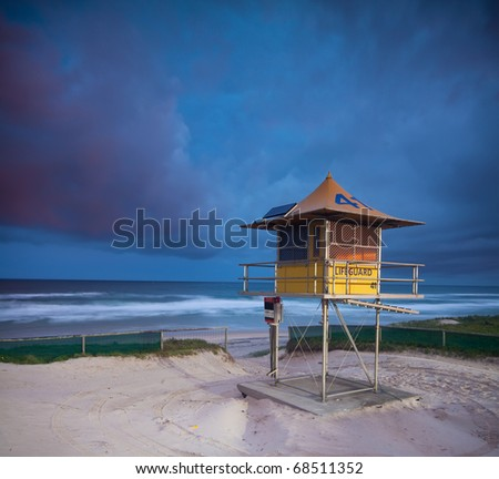 australian beach at twilight with lifeguard hut in foreground - stock photo