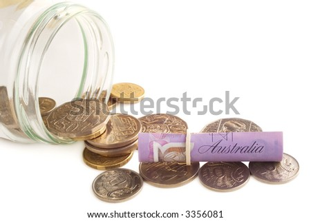 Australian currency tipping out of jar on a light background.