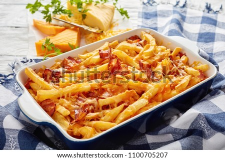 australian fries smothered in melted mix of shredded cheese and bacon in a baking dish on a white wooden table with grated cheese at the background, view from above, close-up