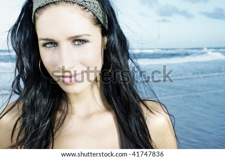 Australian girl on the beach. head shot pretty brunette with head band looking into camera. bright and sunny. slight smile and beautiful eyes.