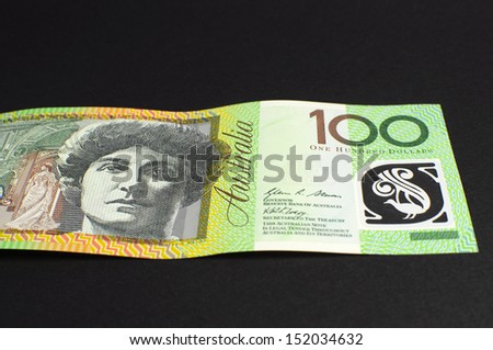Australian green and gold  100 hundred dollar note, against a black background, laying flat.