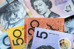 Australian money background.  Focus on foreground, blurred faces beneath.
