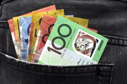 Australian money including 100, 50, 5, 10 and 20 dollar notes, in back pocket of a man's black charcoal jeans pocket.
