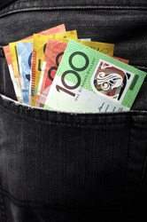 Australian money including 100, 50, 5, 10 and 20 dollar notes, in back pocket of a man's black charcoal jeans pocket. Vertical.