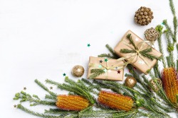 Australian native plant Banksia frames the Christmas inspired background. Gifts, gold ribbon, glitter, cream pine cones and other Christmas decorations on a rustic white background.