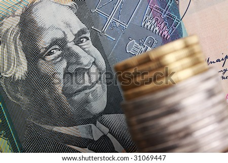 Australian $50 note with coins stacked in foreground. Focus on face of David Unaipon, aboriginal writer and inventor.