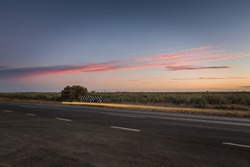 Australian outback landscape, multi-lane highway with colorful clouds at dusk.