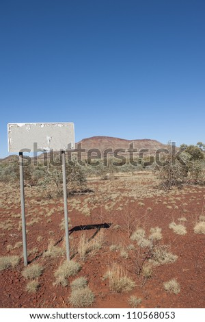 Australian outback landscape, with typical scenery of the Pilbara in Western Australia, red earth, spinifex grass and hills in the background, plus empty sign, blue sky as copy space.