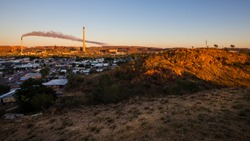 Australian Outback View from the lookout at Mt Isa, Queensland, Australia. Sunrise View of the Copper Mines with smoke coming out of a tower. June, 2019