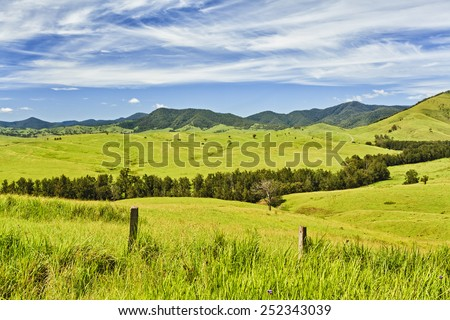 australian rural NSW remote agricultural farm with highly developed grazing land for steer production at cloudy thunderstorm weather view from side road over fence