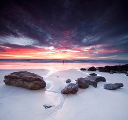 australian seascape at dawn with rocks in foreground (miami beach, queensland, australia)