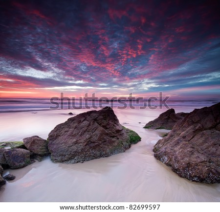 australian seascape at dawn with rocks in foreground (miami beach, queensland, australia)