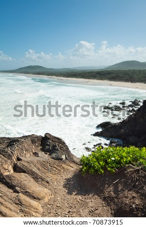 australian seascape during the day with cliff face in foreground (Cabarita Beach,NSW)