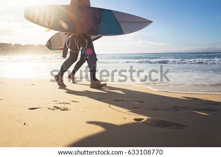 Australian surfers walking along Bondi Beach in the early morning for a surf