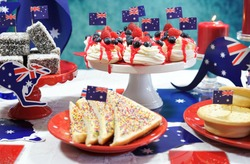 Australian theme party table with flags and iconic food including mini pavlovas, lamingtons, meat pies and fairy bread.