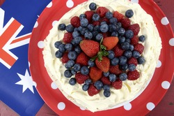 Australian traditional dessert, Pavlova, with whipped cream and strawberries, blueberries and raspberries in red white and blue theme with Australian flag. Overhead.