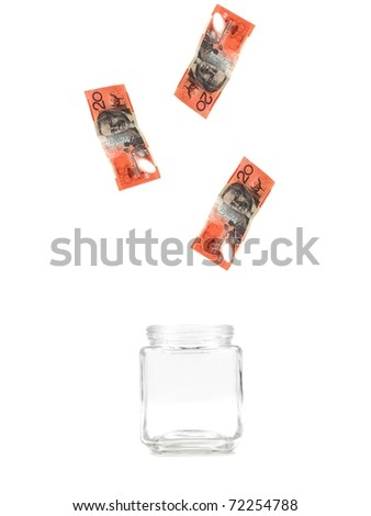 Australian twenty dollar notes floating into a jar isolated against a white background