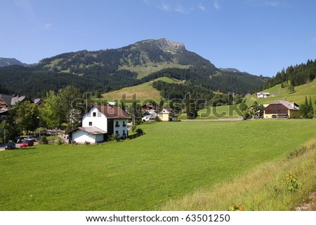 Austria - beautiful alpine village. Small town with green pastures and Alps in background.