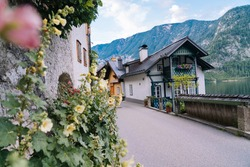 Austria, Hallstatt UNESCO historical village. Colorful town with flowers and historical architecture in Austria Alps mountain. Tourists walk in historical village. Old European place.