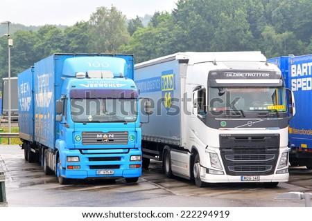 AUSTRIA - JULY 28, 2014: Modern trucks MAN TGA and Volvo FH12 at the interurban freeway.