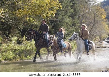 Austria, Salzburger Land, Altenmarkt, Young people riding horses across river