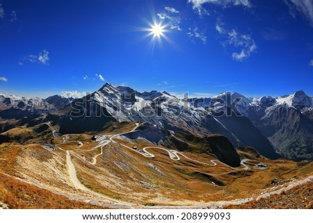 Austrian Alps. Excursion to the picturesque panoramic way Grossgloknershtrasse. Sunny day in early autumn. Great highway winds between hillsides yellowed