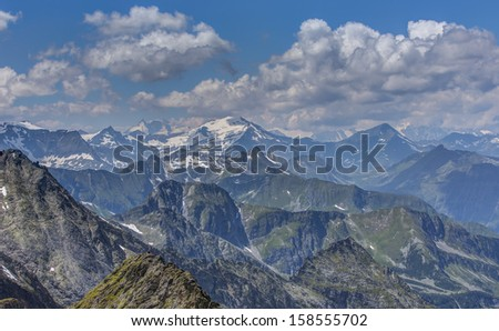 Austrian alps with white couds and blue sky