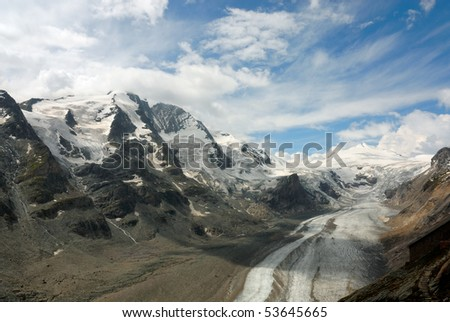 Austrian mountain range and glacier with fluffy white clouds