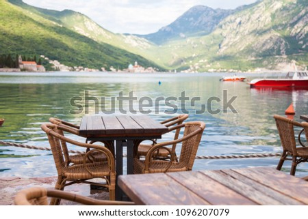 Authentic cafe with wooden rustic tables and wicker chairs. Amazing country landscape with green mountains, sea, boat. Beautiful the Boka Kotor Bay view from Perast in Montenegro. #1096207079