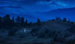 Authentic carpathian house on a mountain hill under the night starry sky. Ukrainian Carpathians, Europe.
