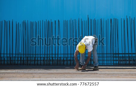 Authentic construction worker installing binding wires to reinforcement steel bars in front of a blue insulated surface prior to cement pouring
