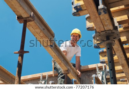 Authentic construction worker placing slab form work beams in construction site