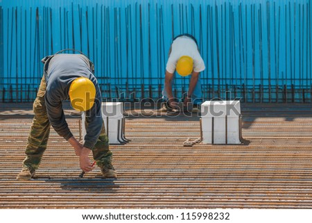 Authentic construction workers installing binding wires to reinforcement steel bars in front of a blue insulated surface prior to pouring concrete