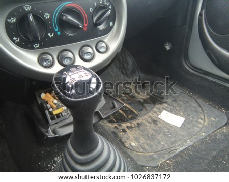 Authentic dirty vehicle interior. Footwell with rubber mat, ashtray and gear stick