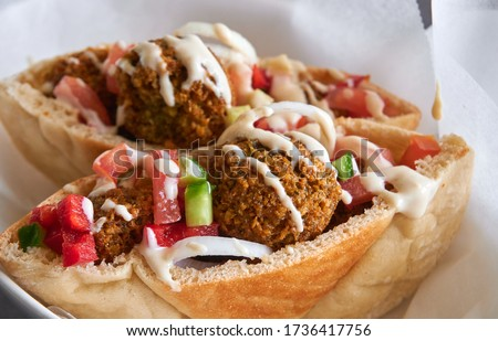 Authentic fresh falafels balls inside of two halves of pita bread sandwich with chopped salad and drizzle of tahini sauce on top, close-up of chickpea falafel in a gluten-free pita Foto d'archivio ©