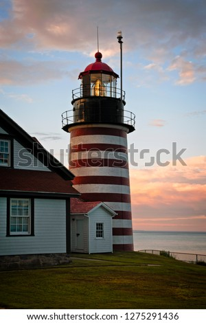 Authentic fresnel lens of West Quoddy head lighthouse, famous for its red and white srtipes, shines brightly during sunset in northern New England. It is the easternmost beacon in America. #1275291436