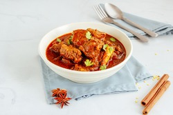 Authentic Lamb Vindaloo Traditional Fiery Red Indian / Goan Curry of Lamb. Lamb Curry / Lamb Vindaloo in a Bowl on White Background with Spoon and Fork.