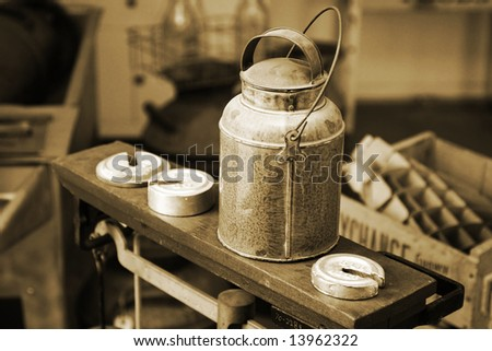 Authentic old-time milk/cream can atop an antique scale with weights in a vintage, historical Creamery setting (vintage tone and grain â?? shallow focus).