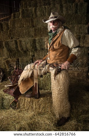 Authentic old west cowboy portrait with wooly chaps, pistol, cowboy hat, leather vest, bandanna in stable