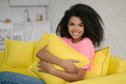 Authentic portrait of cute emotional curly haired girl relaxing and smiling at home. Young attractive African American woman hugging pillow sitting on comfortable yellow sofa at living room