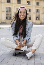 Authentic portrait of smiling asian woman using mobile phone, listening music on the street. Happy emotional  teenager sitting on skateboard looking at camera outdoors. Summertime, positive lifestyle